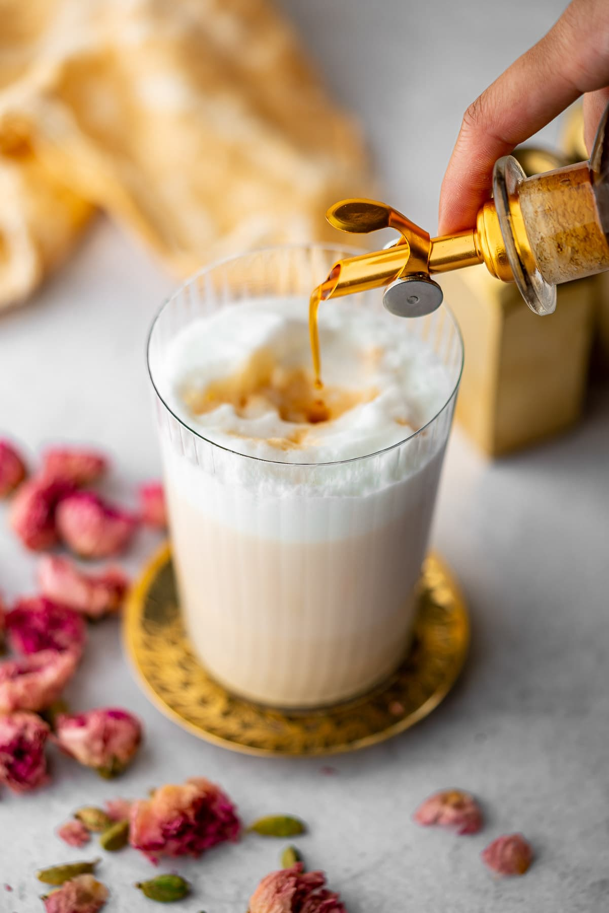 pouring chai syrup into a glass with warm frothy milk