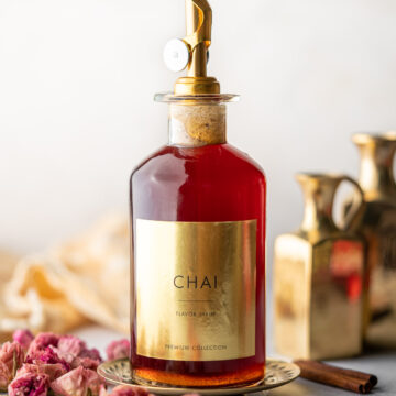 syrup bottle filled with chai syrup with a label decorated with roses and cardamom
