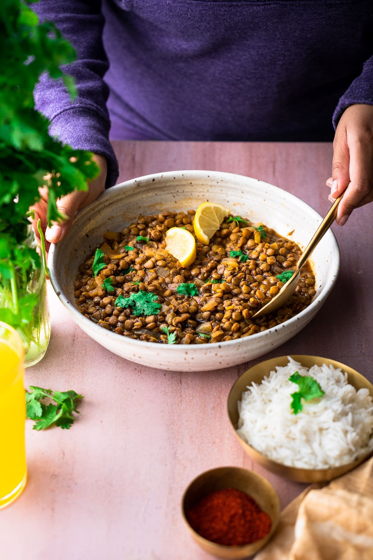 serving sabut masoor dal in a serving bowl with a person spooning it with rice, chili powder, cilantro, and juice alongside