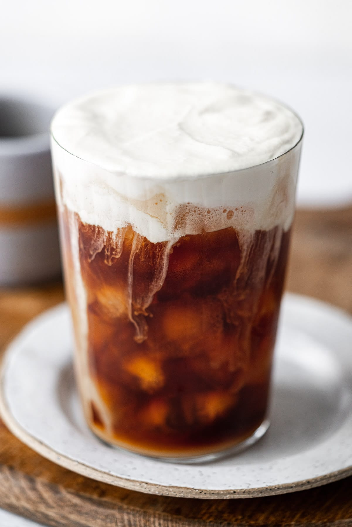 sweet cream cold foam cold brew in a glass on a plate