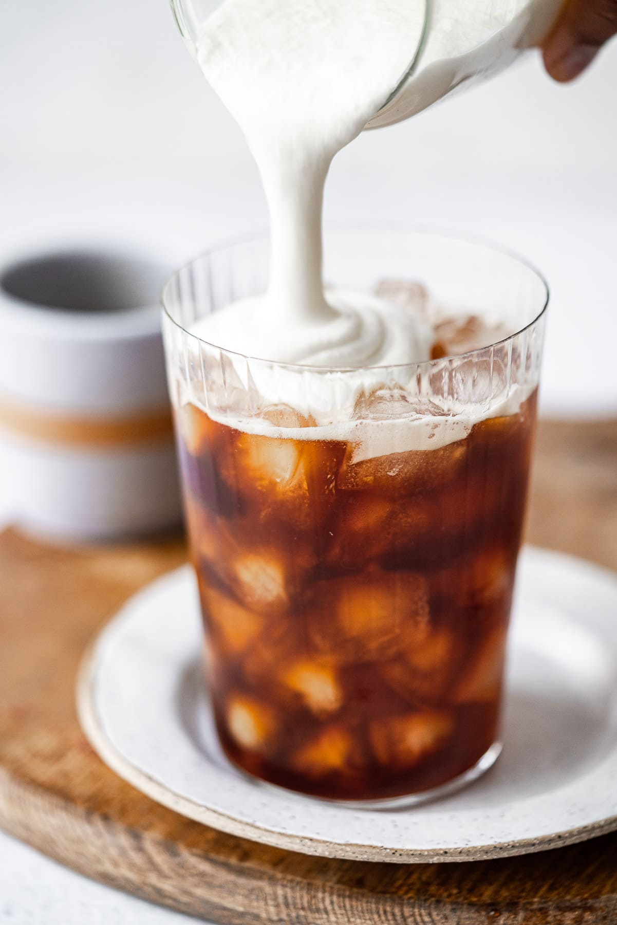 pouring sweet cream cold foam into a cup of iced coffee