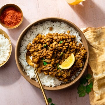 whole masoor dal in a bowl with rice and a gold spoon
